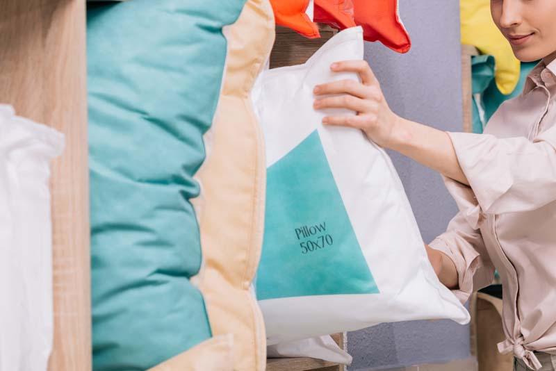 portrait of attractive woman choosing pillow in fu G5KKGDY